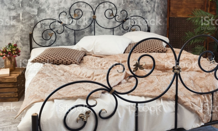 Large double wraought iron bed. Bed is covered with white linens